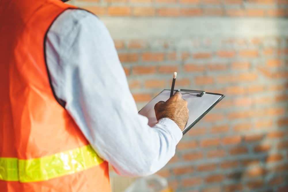 stock-photo-asian-inspector-checking-structure-of-new-property-and-taking-note-in-the-clipboard-for-review-and-1276991476-min