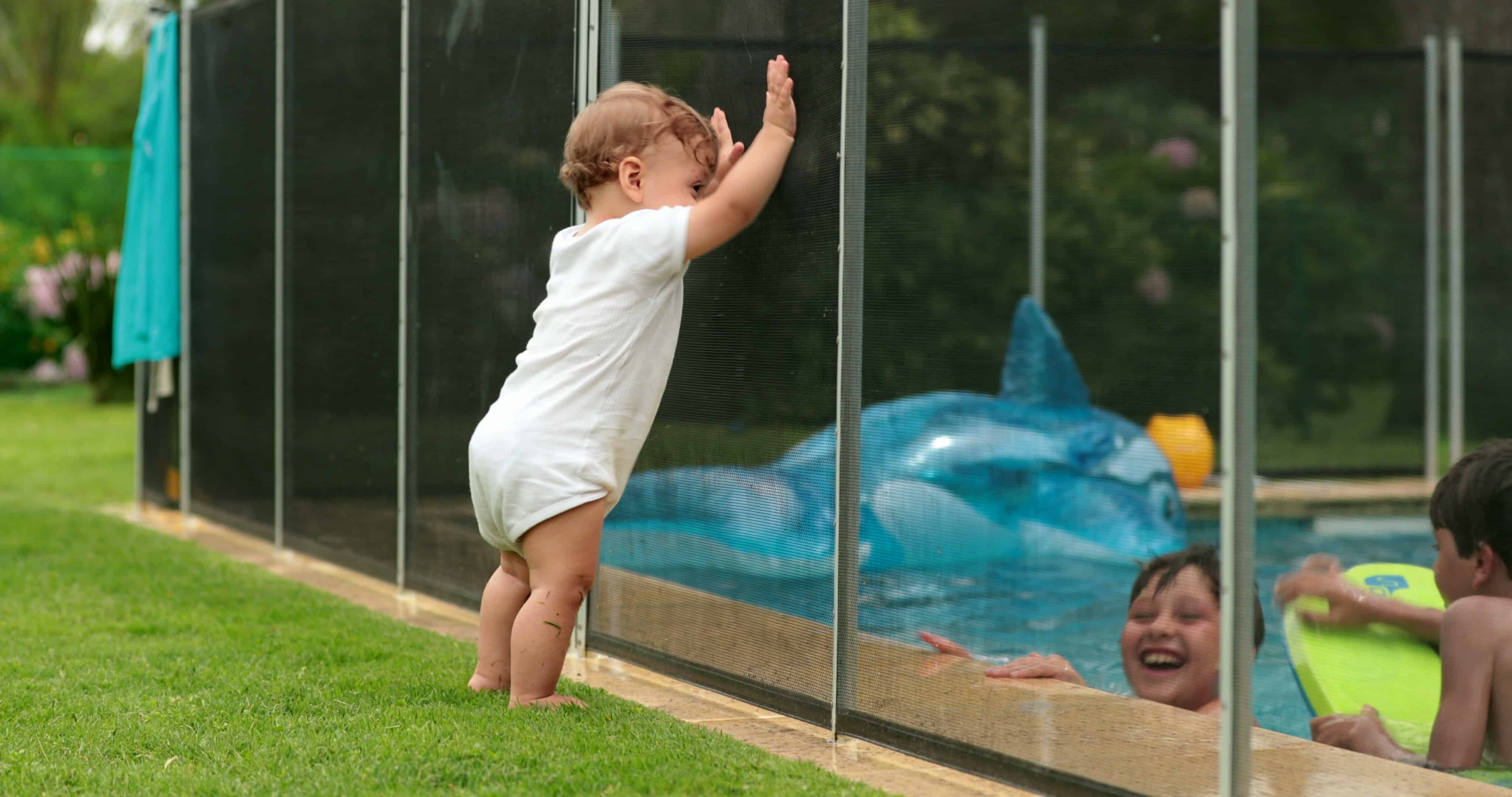 stock-photo--baby-looking-at-kids-play-inside-swimming-pool-water-during-sumemr-day-infant-leaning-on-pool-1672014073-min
