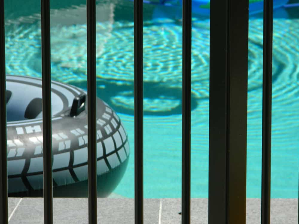 stock-photo-close-up-of-a-pool-as-seen-through-the-safety-fence-1289949979-min