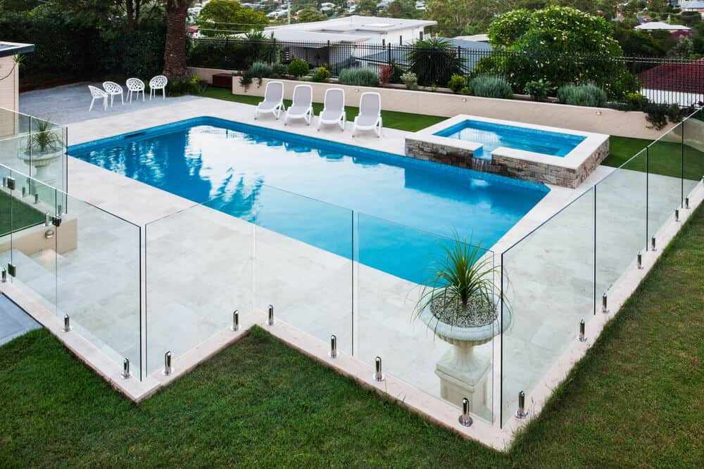 stock-photo-modern-swimming-pool-covered-with-glass-panels-beside-a-green-lawn-garden-including-trees-and-chairs-459414598-min