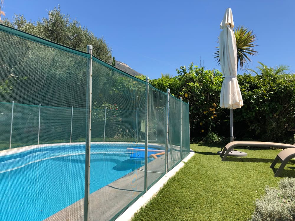 stock-photo-safety-fence-around-a-small-swimming-pool-in-a-back-garden-1443712445
