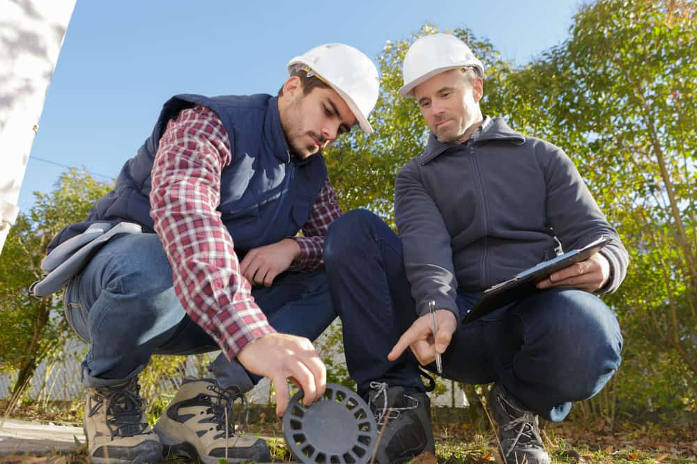 stock-photo-worker-and-manager-inspecting-sewer-drain-742173754-min