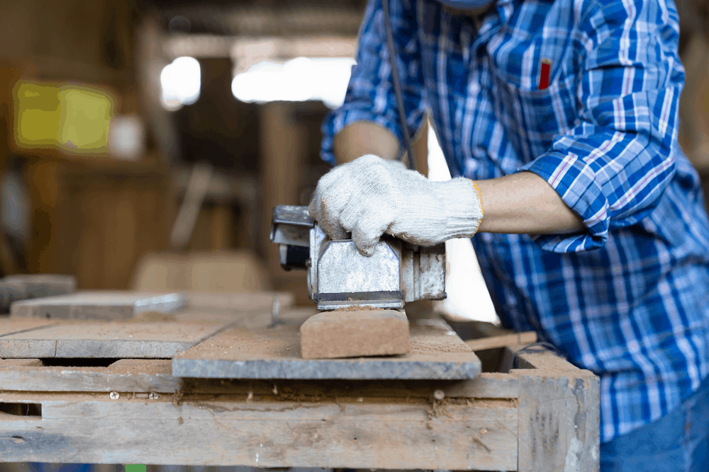 stock-photo-male-carpenter-working-with-electric-wood-planer-on-wood-lath-on-desk-at-woodwork-workshop-male-1925510195