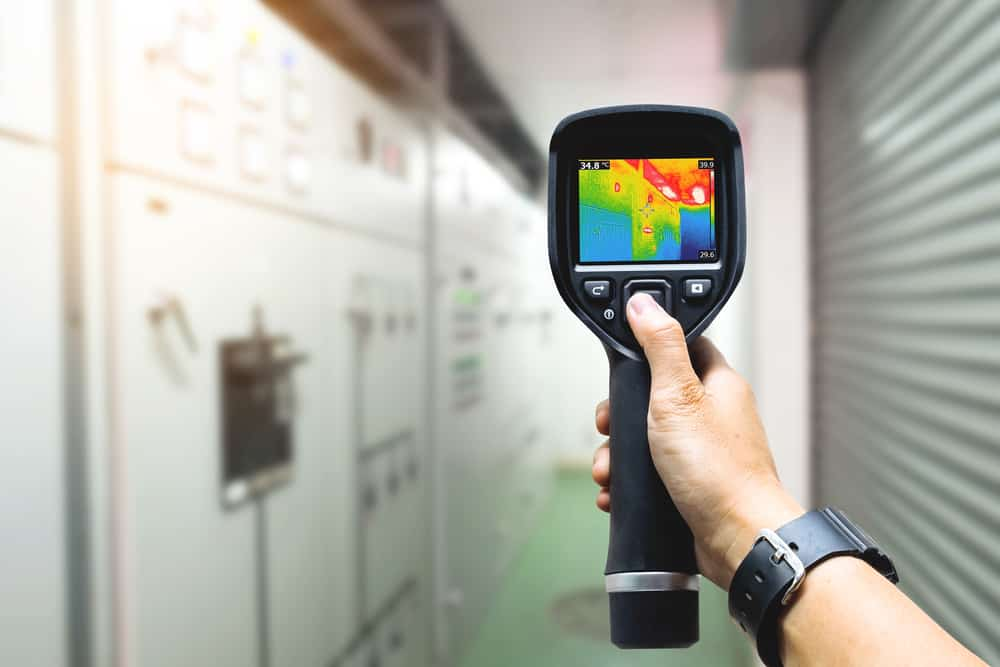 stock-photo-technician-use-thermal-imaging-camera-to-check-temperature-in-factory-488587597