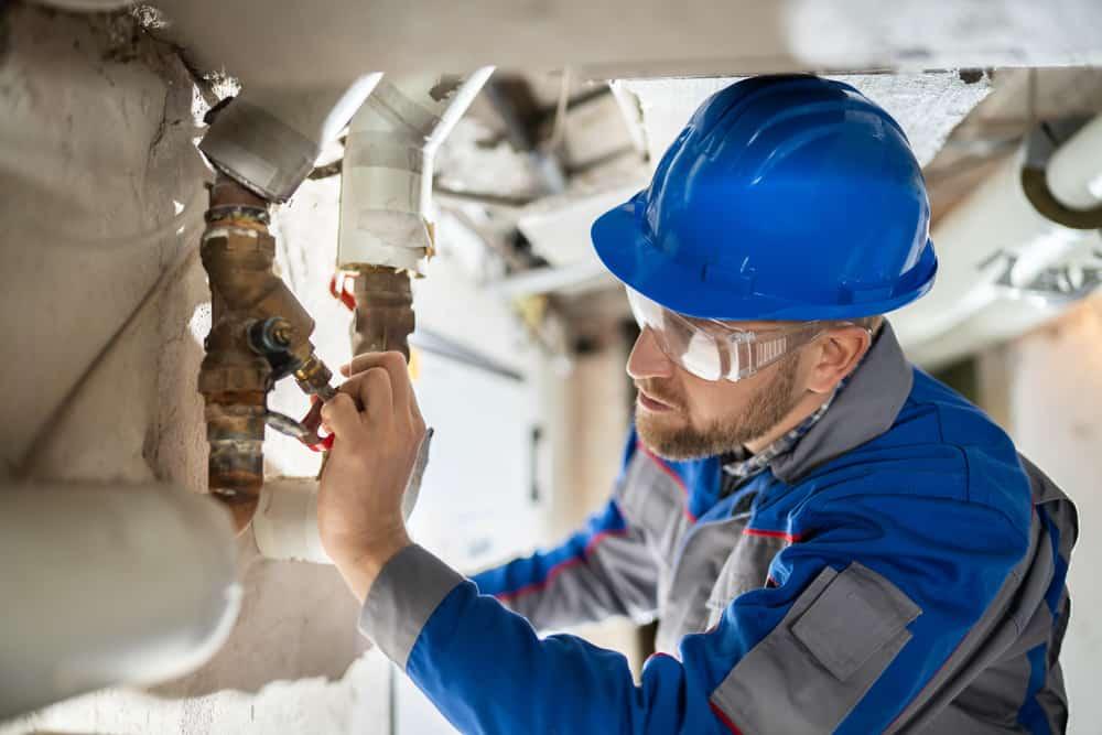 Male,Worker,Inspecting,Water,Valve,For,Leaks,In,Basement